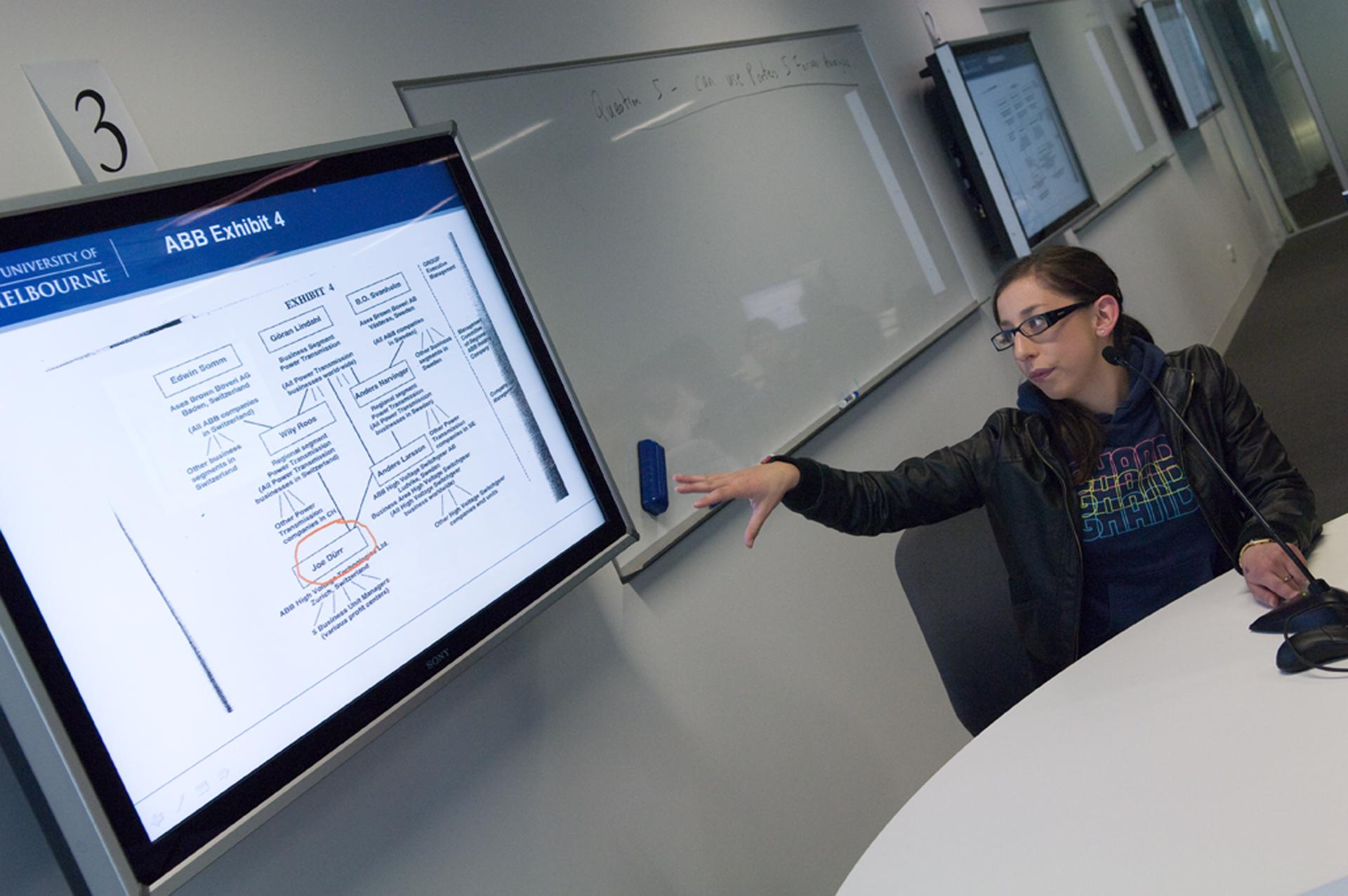 Photo of an academic describing a PowerPoint slide