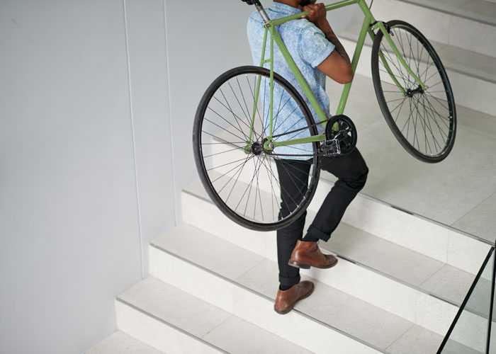 man carrying a bicycle on staircase