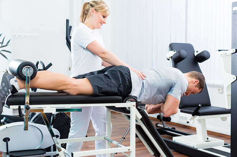 Physiotherapist supervising patient doing exercises on a machine