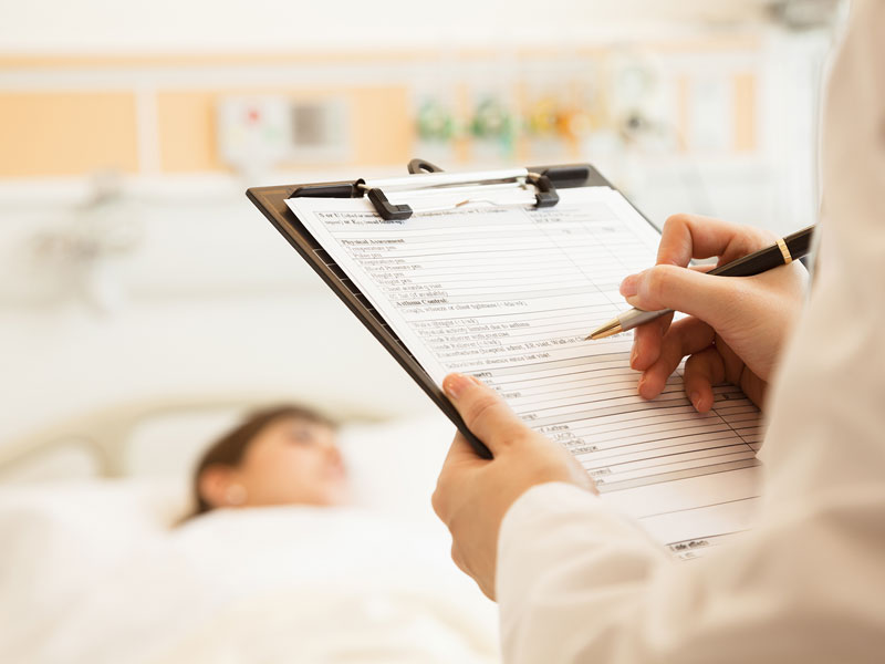 hospital patient in bed whilst doctor takes notes